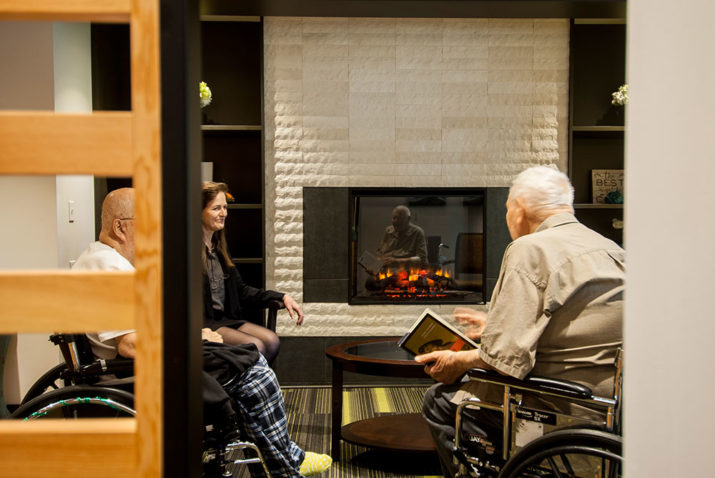 Foss Home residents by fireplace